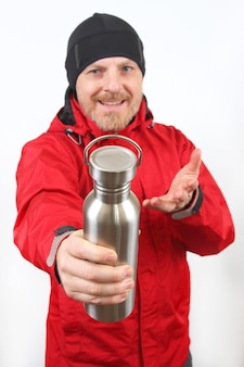 Toeristenreiziger in een rood jasje toont een metalen fles voor water op een witte achtergrond