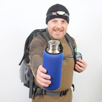 Toeristenreiziger toont een metalen fles voor water op een wit