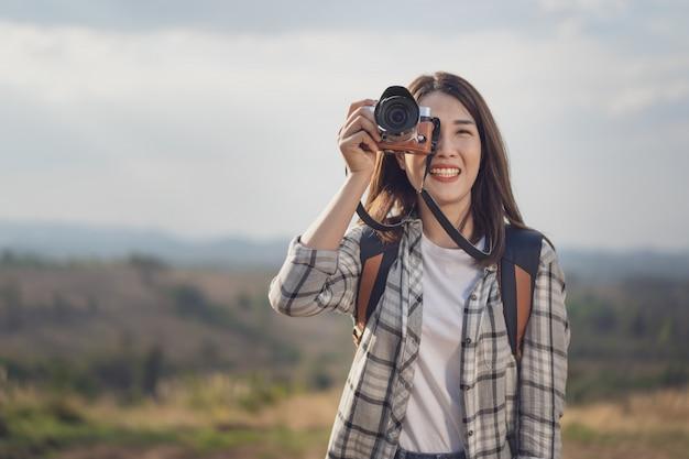 Toeristenvrouw die foto met haar camera in aard nemen