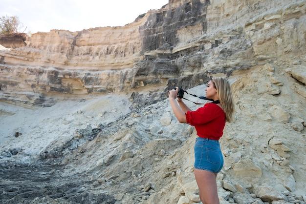 Toeristenvrouw die foto's van de woestijnvallei en rotsen neemt
