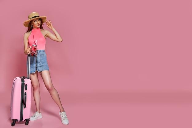 Toeristenvrouw die in de zomer vrijetijdskleding verse drank en koffer op roze achtergrond houden