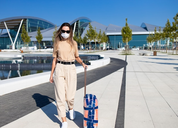 Toeristenvrouw die in gek masker met bagage dichtbij luchthavengebouw lopen