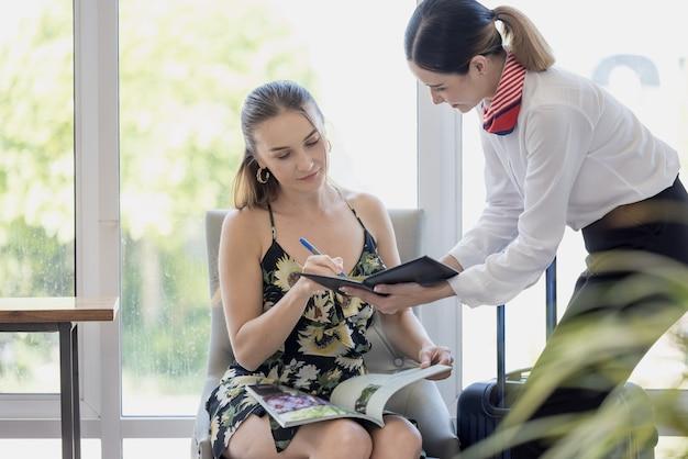 Toeristenvrouw gaat het registratieformulier van het hotel inchecken bij de receptie, kundenservice bij aankomstbestemming voor zomervakantie invullen en ondertekenen