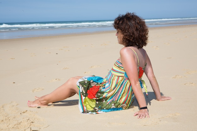 Toeristenvrouw het ontspannen op het strand in vakanties het zitten
