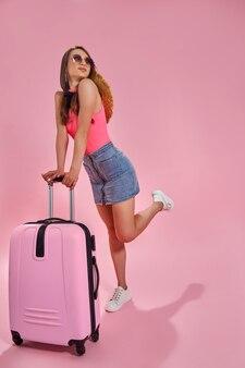 Toeristenvrouw in de zomer vrijetijdskleding op roze background
