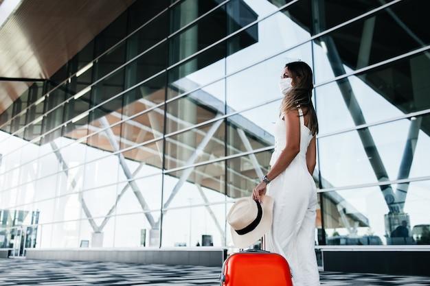 Toeristenvrouw in gekke masker die zich met bagage dichtbij luchthaven bevinden