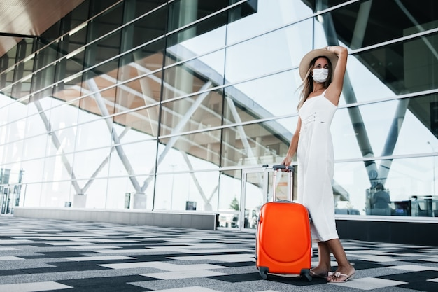 Toeristenvrouw in gekke masker die zich met bagage dichtbij luchthavengebouw bevinden