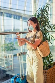 Toeristenvrouw in gezichtsmasker om virus op internationale luchthaven te verhinderen. handdesinfecterend middel op openbare plaatsen ter bescherming tegen virussen en ziekten