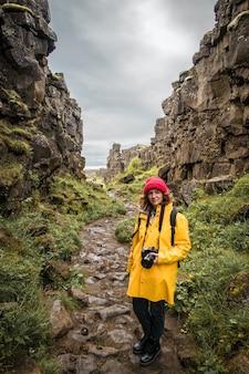 Toeristenvrouw met rugzak die zich dichtbij mooie rotsen van ijsland bevindt