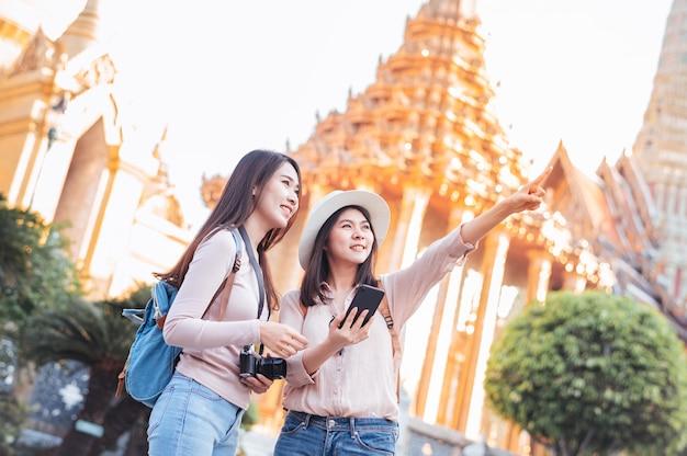 Toeristenvrouwen genieten van reizen in de tempel in bangkok, thailand