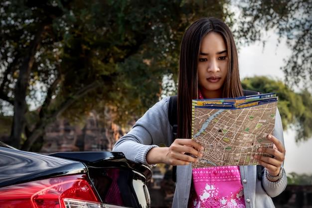 Toeristenvrouwen met het dragen van een rugzak die kaart bekijkt.
