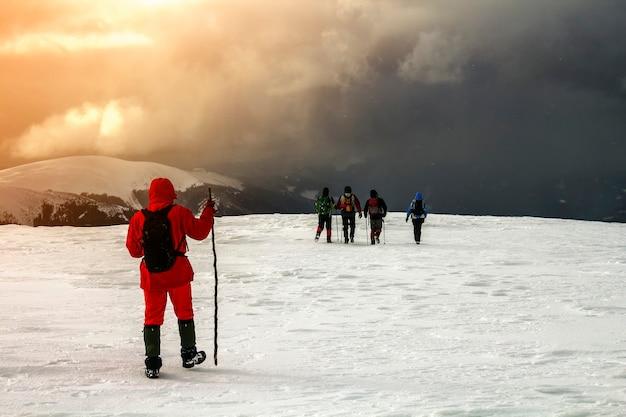 Toeristenwandelaars in de winter besneeuwde bergen en dramatische wolken in de lucht