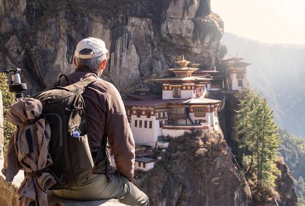 Toeristenzitting op zijn rug die op de tempel van het tijger` s nest in paro, bhutan letten