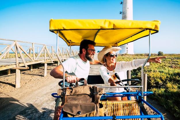 Toeristisch en toerisme mensen concept met vrolijk en gelukkig volwassen paar op een surrey fiets genieten van de outdoor vrijetijdsbesteding op vakantie zomervakantie seizoen samen