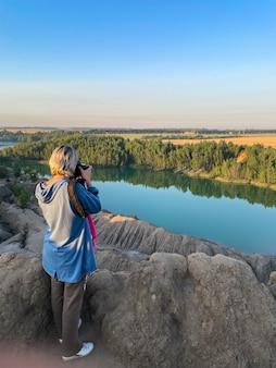 Toeristisch meisje houdt in handen neem fotografie klik op moderne fotocamera