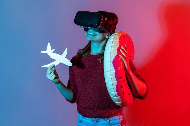 Toeristisch meisje in vr-bril met rubberen ring en vliegtuigmodel, kijkend naar virtuele reistours