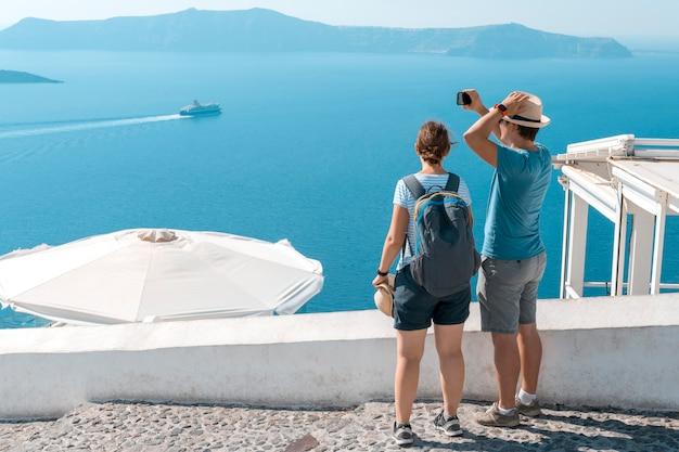 Toeristisch paar genietend van uitzicht op het eiland santorini en de caldera in de egeïsche zee