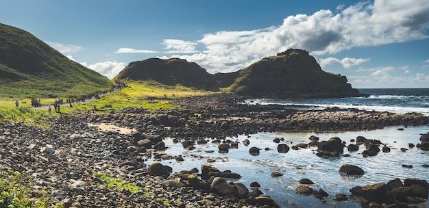 Toeristisch pad naast de kustlijn van noord-ierland. geweldig iers landschap. groene bedekte heuvels onder de blauwe bewolkte hemel. boulders strand. outdoor wandelactiviteit. toeristische attractie.