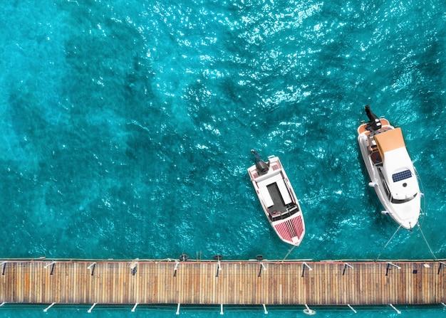 Toeristisch plezierjacht en motorboot op zee nabij de pier.