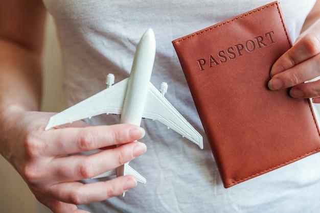 Toeristische benodigdheden. vrouwelijke vrouwenhanden die klein stuk speelgoed modelvliegtuig en paspoort houden