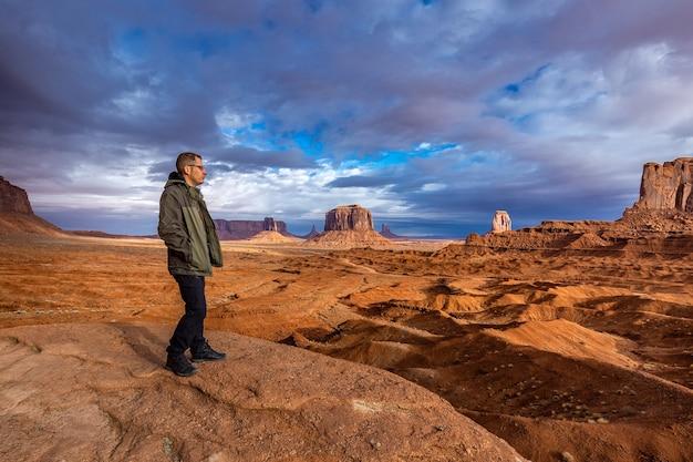 Toeristische bewonderende weergave met storm op de achtergrond in monument valley, arizona, usa.