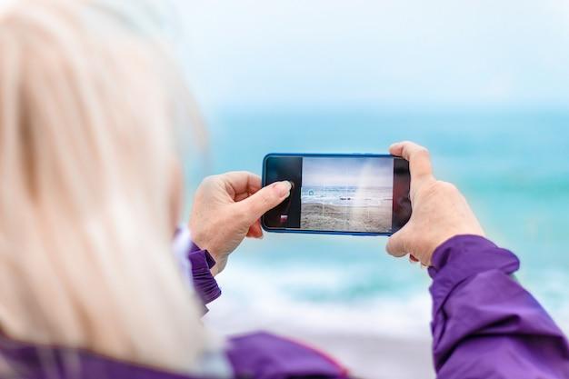 Toeristische blanke blonde vrouw fotograferen via de telefoon op het strand bij de oceaan