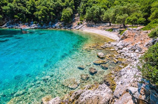 Toeristische boot voor anker in een turkoois gekleurde baai, eiland kefalonia, griekenland