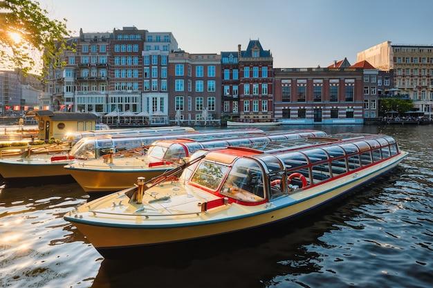 Toeristische boten afgemeerd in amsterdamse kanaalpijler op zonsondergang
