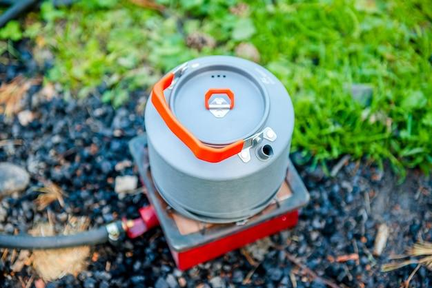 Toeristische gasketel in de natuur een waterkoker die kookt op een kampeerfornuis om thee te zetten tijdens het kamperen