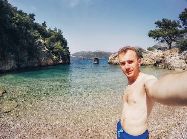 Toeristische gefotografeerd tegen de achtergrond van de zee.
