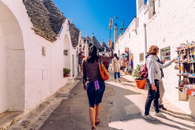 Toeristische gids die een groep bezoekers van de prachtige reis van de stad alberobello begeleidt.