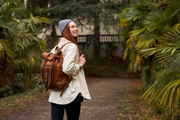 Toeristische jonge vrouw loopt door het bos of de tuin met bomen in de buitenlucht die interesse hebben om...