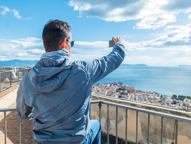 Toeristische jongeman selfie en hij is een foto van de smartphone in de oude stad in de stad bern