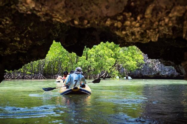 Toeristische kano door kleine grot naar mangrovebos