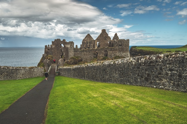 Toeristische lopen naar de hoofdingang van dunluce castle