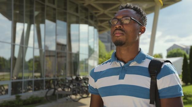 Toeristische man die foto's maakt met cameratelefoon buiten jonge afro-amerikaanse man die foto's maakt op telefoon op straat