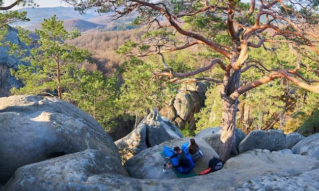 Toeristische man en vrouw in slaapzakken op grote rotsen Premium Foto