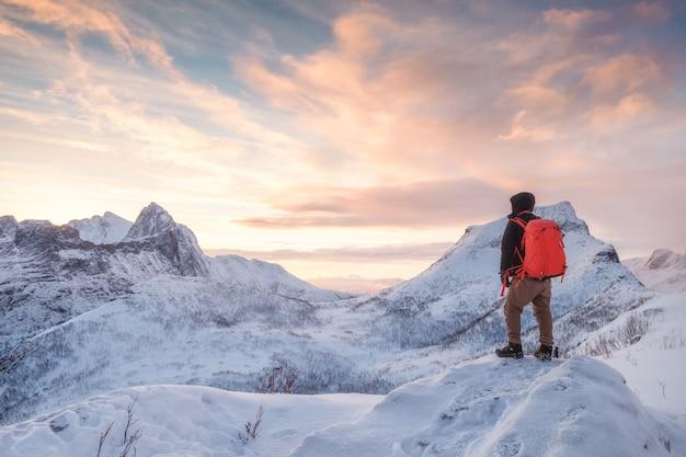 Toeristische man klimt op top besneeuwde berg