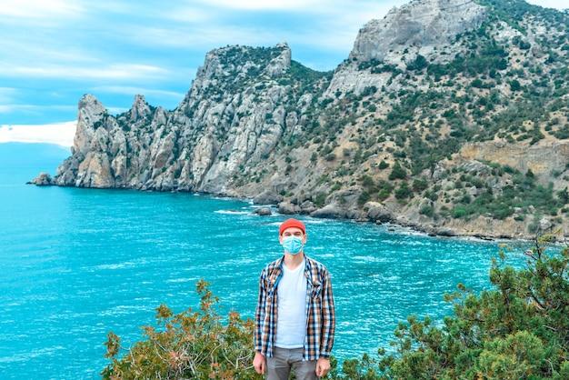 Toeristische man met een masker op vakantie aan zee met een prachtig uitzicht. zomer reisconcept