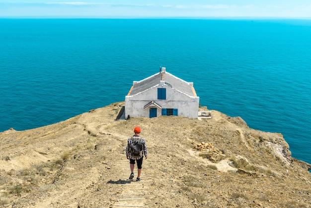 Toeristische man met een rugzak loopt langs de weg naar de zee. levensstijlconcept.