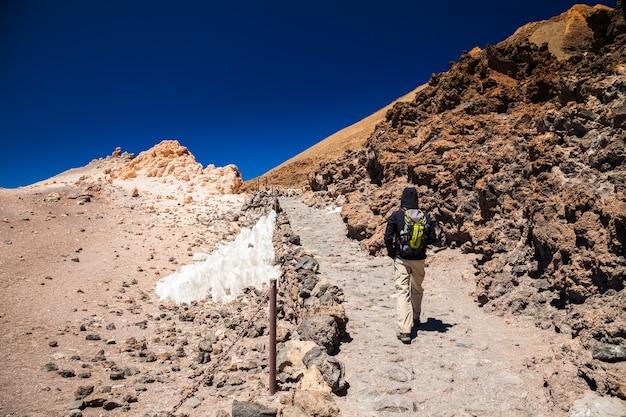 Toeristische man met rugzak naar de top van de vulkaan teide in tenerife, canarische eilanden, spanje