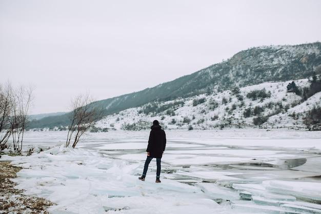 Toeristische man staat op een ijsschots op de achtergrond van een bevroren rivier op een bewolkte dag. winter avontuur.