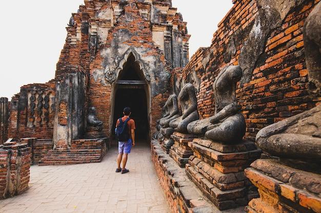 Toeristische mannelijke schoudertas die in de buurt van oude verwoeste stoepa loopt met fotocamera in ayutthaya historical park, thailand