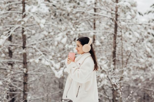 Toeristische meisje in winterkleren houdt kopje thee in handen. sneeuw behandelde dennen op de muur.