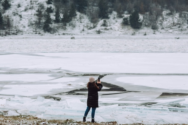 Toeristische meisje reizen op bevroren rivier en het nemen van foto winterlandschap. meisje op wintervakantie.