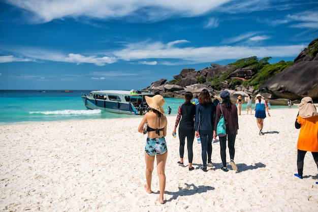 Toeristische mensen lopen op het witte zandstrand van het eiland koh similan no.8 om een speedboot te nemen na een bezoek aan het zeilrotsoriëntatiepunt in de zomer, phang nga, thailand.