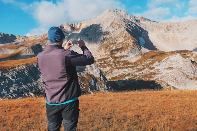 Toeristische reiziger fotografeert bergen bedekt met wolken op een smartphone