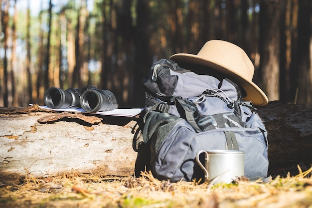 Toeristische rugzak, hoed, verrekijker en een kaart op een logboek in het bos. concept wandelen, wandelen in de bergen.