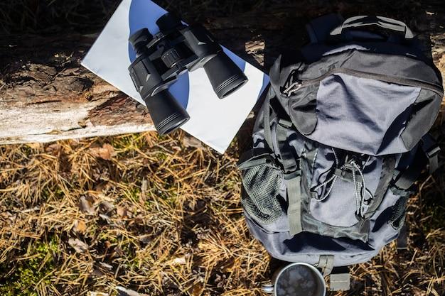 Toeristische rugzak, hoed, verrekijker en een kaart op een logboek in het bos