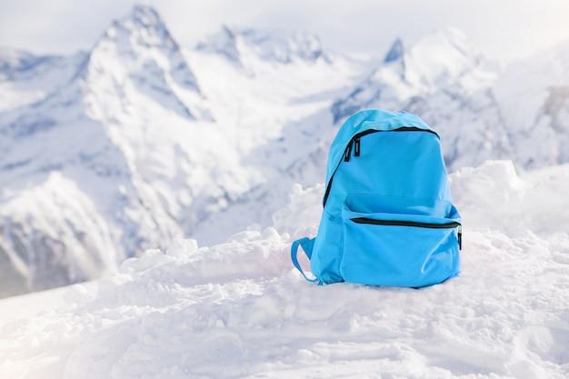 Toeristische rugzak op de achtergrond van besneeuwde bergen